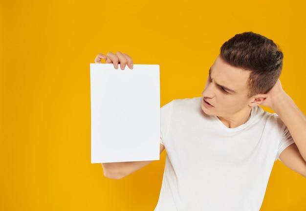 Man in white tshirt blank sheet of paper presentation yellow background