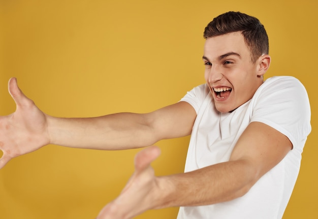 Man in white tshirt gesturing with his hands yellow background