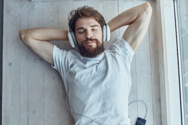 Man in white tshirt lying on the windowsill wearing headphones hipster