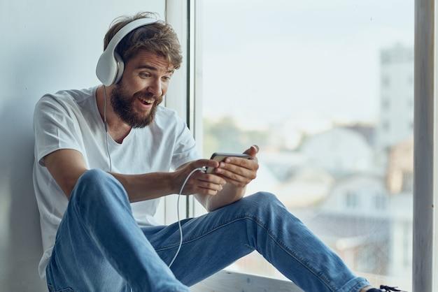 Man in white tshirt sitting on the windowsill in headphones in headphones