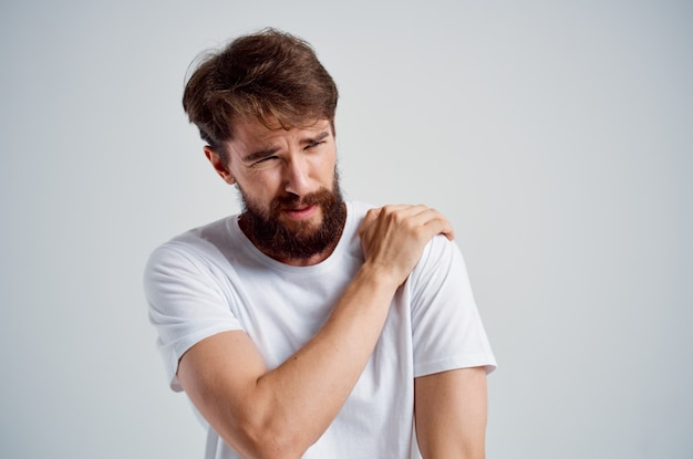 Man in a white tshirt stress medicine pain in the neck studio treatment