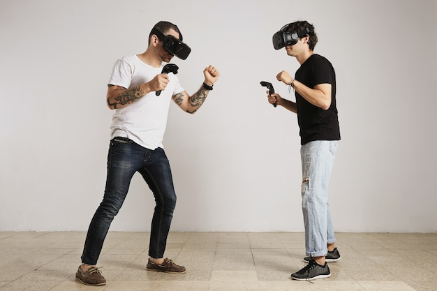 A man in white unlabeled t-shirt with bear and tattoos and a man in black unlabeled t-shirt wearing vr headsets fight in a room with white walls.