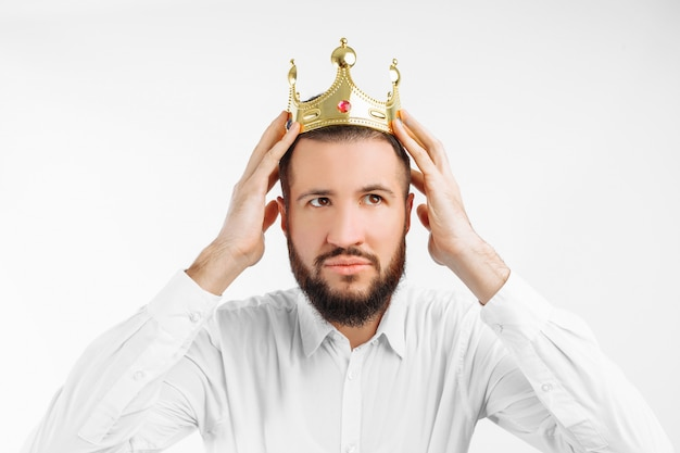 A man on a white wall, wears a crown on his head,