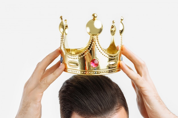 Man on a white wall wears a crown on his head,