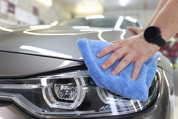 Мужчина, который украшает автомобили, держит в руке микрофибру и полирует концепцию автомойки