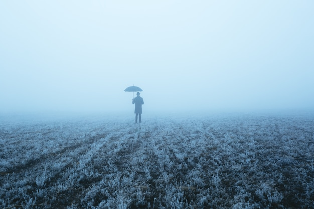 A man who goes on a field with thick fog and holds an umbrella. conceptual image