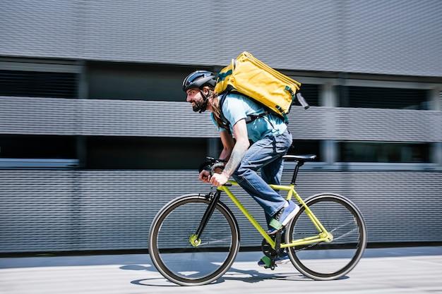 Человек, который работает, доставляет еду курьером на высокой скорости по городу.