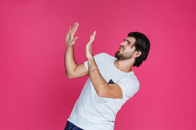 그의 손을 크게 벌리고 무언가를 멈추려 고하는 남자.