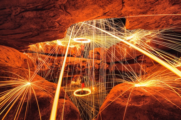 Man wielding spark fire swirl in stone hole cave and pond reflection in the night at sam phan bok, ubon ratchathani