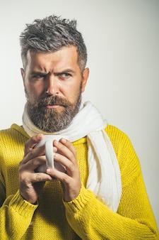 お茶やコーヒーのひげを生やした男を保持している口ひげを持つ長いひげの残忍な白人ヒップスターを持つ男
