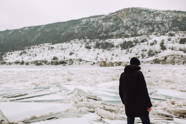 Man in winter clothes on a background of the frozen river with big ice floes.