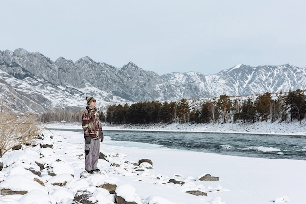 Man in winter clothes in cold winter weather with mountains, river and snow