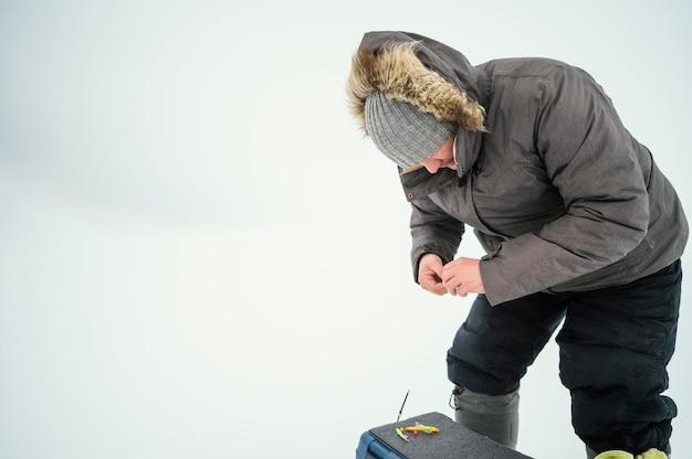 Uomo in abiti invernali che pesca da solo all'esterno