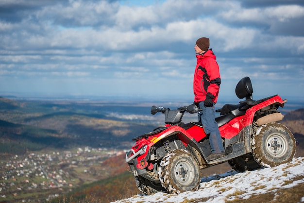 Man in winter clothes standing on a red quad bike