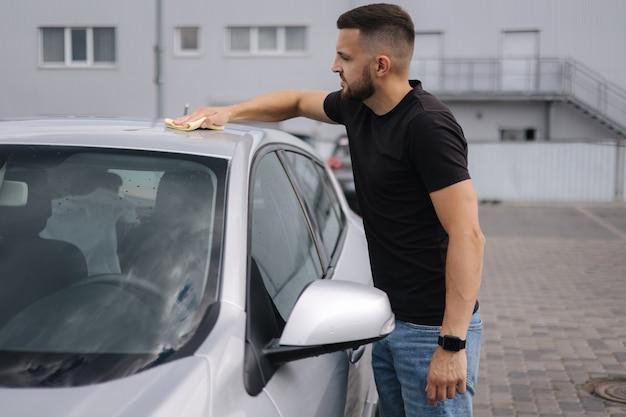 Мужчина вытирает ветровое стекло своей машины тряпкой в автосалоне на автомойке самообслуживания