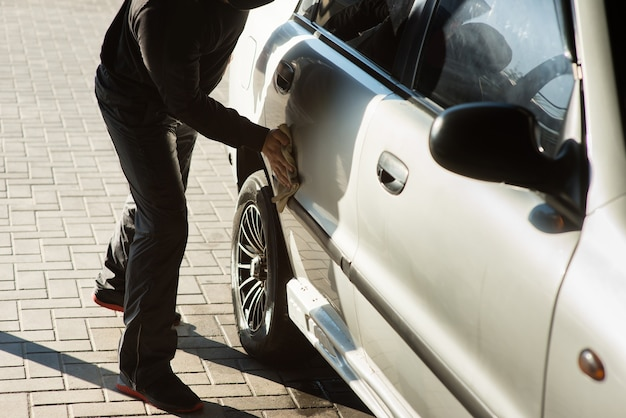 A man wipes a car at a self-service car wash