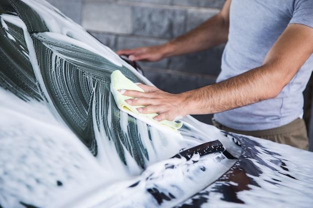 A man wipes the foam on the car with a rag. car wash