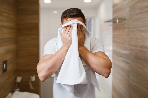 男はタオルで顔を拭く