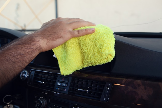 A man wipes the interior of a car with a rag