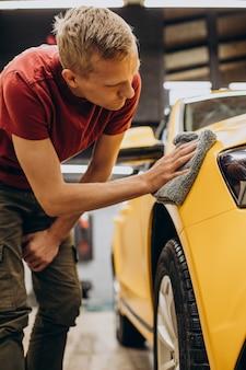 Мужчина вытирает машину микрофиброй после стирки