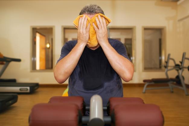 Человек вытирает лицо полотенцем после тренировки
