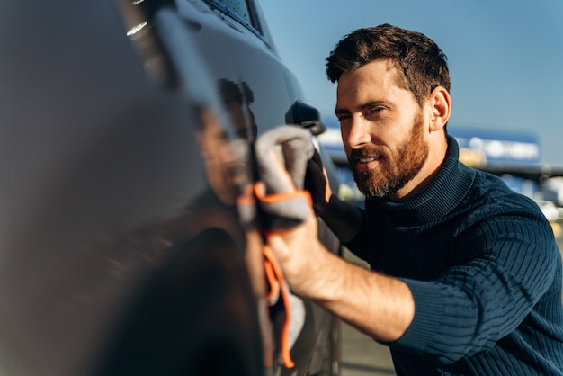 Man wiping his car at the street. car detailing wash during the sunny day. handsome bearded man in casual wear washing car doors and hood with microfiber cloth
