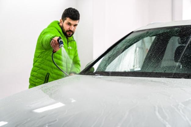 緑のコートを着た男が高圧ホースから泡で水を噴霧して車を洗う