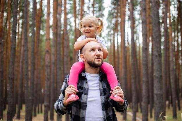 バックパックを背負った男は、森の中で子供を肩に乗せています。山や森への家族のハイキング。