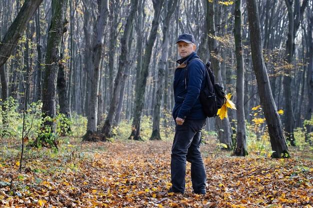 秋の森でリュックを背負った男