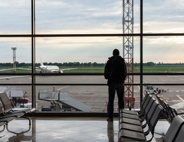 그의 어깨에 배낭을 든 남자는 공항, 항공 관광의 비행기에서 창 밖을 내다 본다.