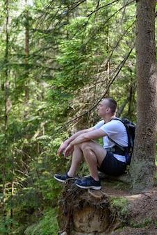 절벽에 침엽수 림 숲에 앉아 배낭을 가진 남자. 수직 프레임. 프리미엄 사진