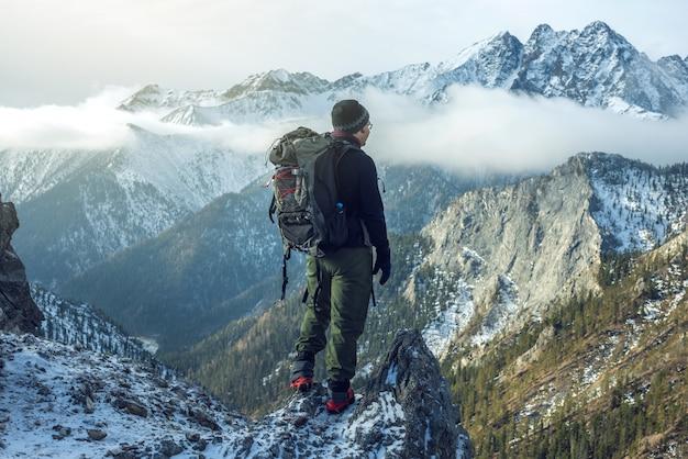 山の上に立っているバックパックを持つ男