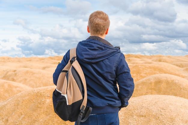 Человек с рюкзаком стоит в пустыне