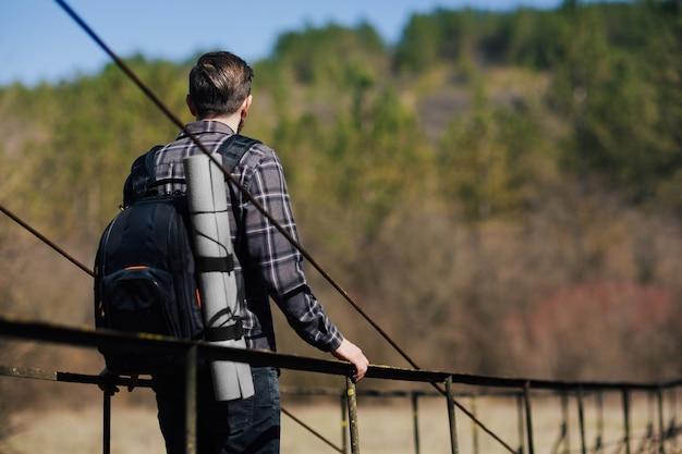 バックパックを持った男が吊橋を渡って歩く