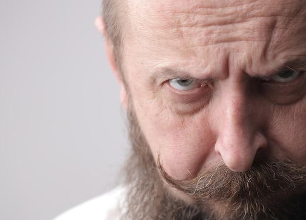 灰色の壁の前に立っている間眉をひそめているひげと口ひげを持つ男