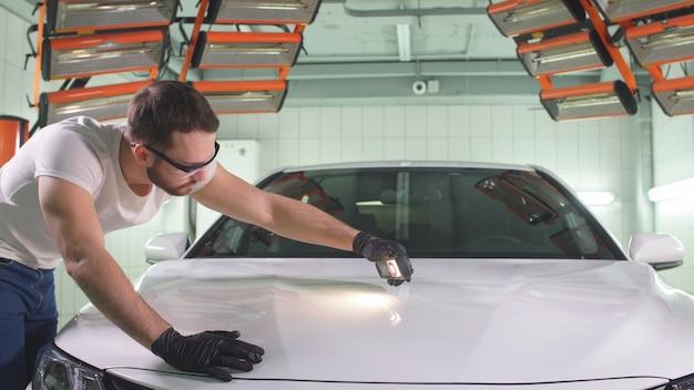 Мужчина с бородой и в перчатках с фонариком занят проверкой качества полировки кузова автомобиля