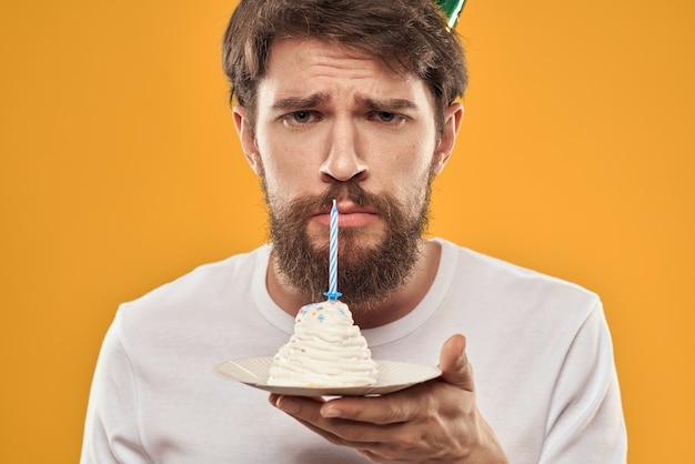 あごひげを生やして、誕生日パーティーを祝う帽子をかぶった男