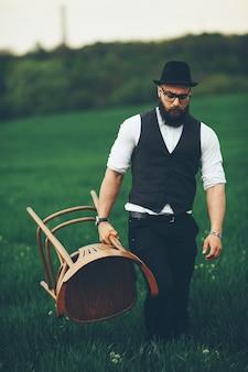 緑の野原でひげとサングラスを持った男