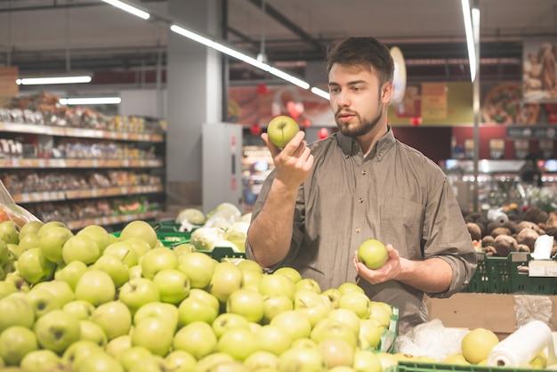 ひげを持つ男が店でリンゴを選ぶ