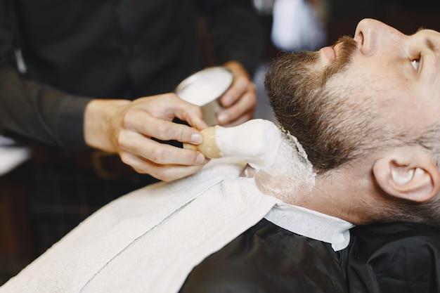 あごひげを生やした男。クライアントと美容師。ブラシを持つ男。