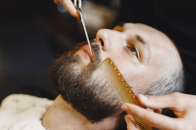 あごひげを生やした男。クライアントと美容師。くしとはさみを持つ男