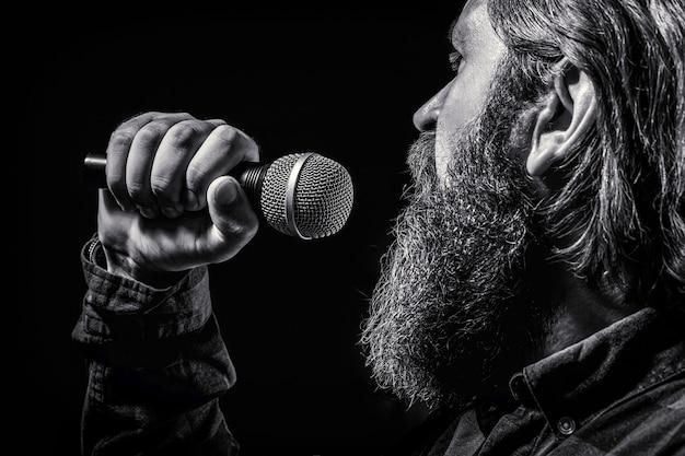 마이크를 잡고 노래하는 수염을 기른 남자. 노래방에서 수염 난 남자는 마이크에 노래를 부릅니다. 남자는 노래방에 참석합니다. 검정색과 흰색.