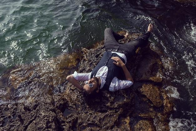 크림 타르칸쿠트의 돌 해변에 검은 옷과 흰 셔츠를 입은 수염을 기른 남자