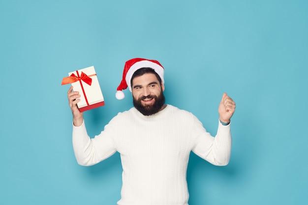 クリスマスと新年のスタジオでポーズをとってひげを持つ男