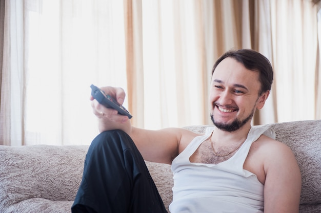 Человек с бородой сидит на диване