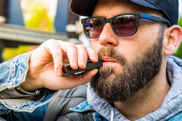 あごひげを生やした男が電子タバコを吸う