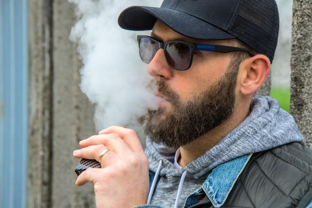 Мужчина с бородой курит электронную сигарету