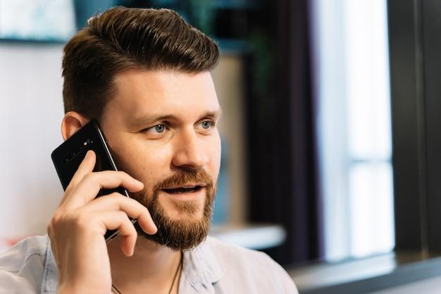 彼の携帯電話に話している間、ひげを持つ男がリモートで作業しています