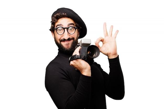Человек с беретом и очки смотреть со старой видеокамеры