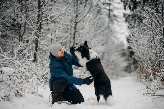 Человек с черно-белой собакой бордер-колли в снегу